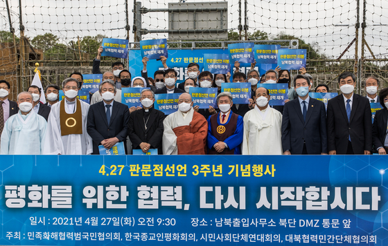 Civic and religious groups pose for a photo at an entrance to the Demilitarized Zone (DMZ) in Paju, Gyeonggi, on Tuesday, to commemorate the third anniversary of the inter-Korean summit in Panmunjom on April 27, 2018. They urged the two Koreas to resume talks to pave the way to peace. [JOINT PRESS CORPS]
