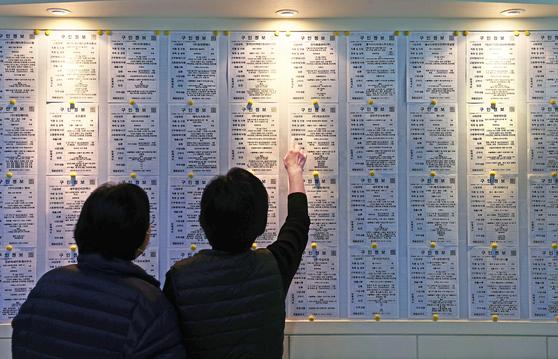Visitors look at job postings at a job center in Seongdong District, eastern Seoul, in November. [YONHAP]