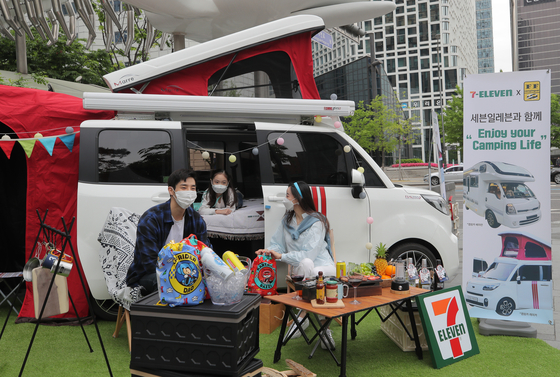 Models pose in front of a camping car displayed at 7-Eleven's headquarters in Jung District, central Seoul on Tuesday. The convenience store said it is selling two camping car models in collaboration with Bayrun RV Group, a Korean RV company that officially launched in March. The camping car, which is a remodeled Kia Ray, retails at 29.15 million won ($26,000), while the larger Bayrun 640 RV is sold for 76.5 million won. [YONHAP]