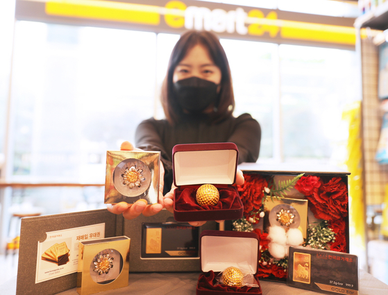 A model holds up a golden carnation and golf ball at Emart24 headquarters in Seongdong District, eastern Seoul, on Tuesday. The convenience store arm of retail giant Emart said it is selling different gold-colored products including the golden carnation, golden golf balls and gold bars in collaboration with Korea Gold Exchange ahead of Parents' Day on May 8. Children traditionally show their appreciation to their parents on the holiday by presenting them with carnations. [EMART]