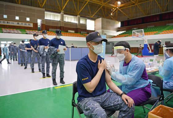 A Marine receives an AstraZeneca vaccine shot at the Jinhae Naval Base in Changwon, South Gyeongsang, on Wednesday, as the country began inoculating troops age 30 and older. No specific plan has been made for around 455,000 soldiers under the age of 30. [YONHAP]