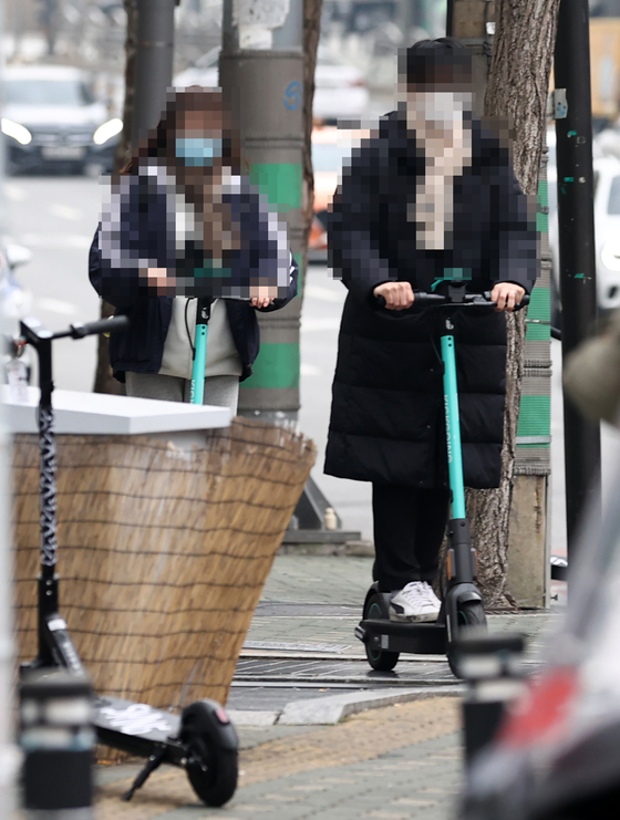Two people ride e-scooters in Seoul [YONHAP]