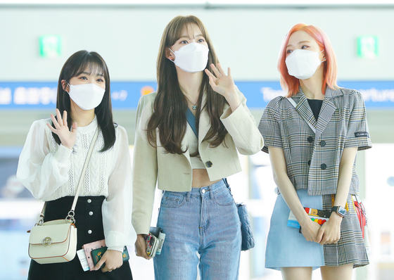 """From left, Nako Yabuki, Sakura Miyawaki and Hitomi Honda, Japanese members of girl group IZ*ONE, leave Korea for Japan via Incheon International Airport on Thursday afternoon. IZ*ONE formed through the 2018 Mnet audition show """"Produce 48"""" and disbanded this month after its contract expired. [ILGAN SPORTS]"""
