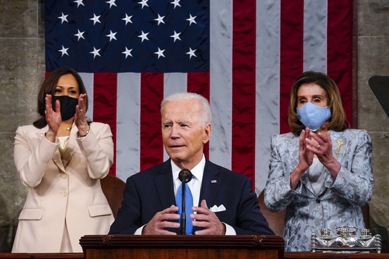 U.S. President Joe Biden, center, makes his first formal address to a joint session of Congress Wednesday in Washington, with Vice President Kamala Harris and House Speaker Nancy Pelosi applauding behind him. [AP/YONHAP]
