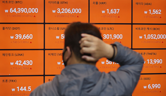 A passerby looks at prices of cryptocurrencies including bitcoin on a digital signboard operated by a local cryptocurrency exchange, Bithumb, in Gangnam District, southern Seoul, on Thursday. [YONHAP]