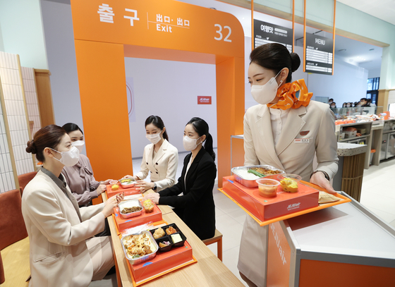 Jeju Air flight attendants serve in-flight meals at Jeju Air On The Table, the airline's new cafe in AK& Hongdae in Mapo District, western Seoul. Jeju Air's in-flight meals, including bulgogi bowls and black pork belly with rice, will be offered for visitors to enjoy. The cafe will be open for three months from Thursday. [YONHAP]