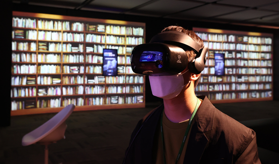"""A visitor wears a VR device to experience a library of the future at the National Library of Korea's new exhibition """"The Live Library"""" that runs until May 31. [YONHAP]"""