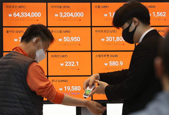 A Bithumb employee checks a visitor's temperature at its office in Gangnam District, southern Seoul, on Thursday. Cryptocurrency exchanges, which have shut down their customer centers due to the Covid-19 pandemic, have been reopening amid the cryptocurrency boom in Korea. [YONHAP]
