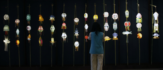 """A visitor admires different lanterns on display at the """"Yeondeunghoe: Lighting up the mind and the world"""" exhibit at the Central Buddhist Museum in central Seoul. [NEWS1]"""