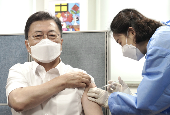 President Moon Jae-in, left, receives the second dose of the Covid-19 vaccine at the Jongno District Public Health Center on Friday. He received the second doze of the AstraZeneca vaccine earlier than scheduled in order to visit Washington for his summit with U.S. President Joe Biden on May 21. [YONHAP]