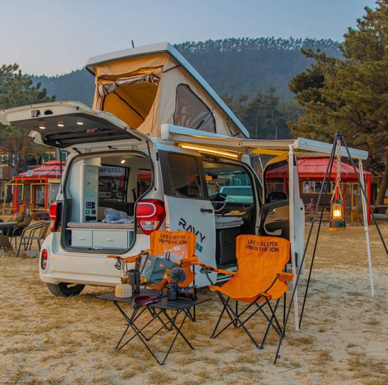 """A Kia Ray customized by campervan-maker DaonTnT and nicknamed the Kia Ravy is parked at a campsite. Homeplus held an event on Monday, renting out the vehicle for free to celebrate Korea's """"family month."""""""