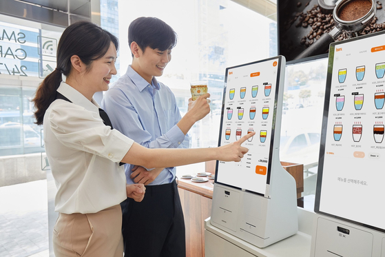 Models use a digital kiosk developed by Samsung Electronics to order drinks at the C+Urban Smart Cafe located in Gangnam, southern Seoul. Samsung Electronics announced Monday it would be supplying its self-ordering kiosk systems to coffee chain C+Urban. [YONHAP]