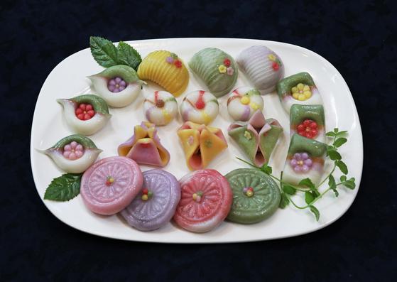 Kim's various flower-shaped tteok: 'Baram-tteok' (half-moon shaped rice cakes filled with bean paste), 'kkot-sanbyeong' (flower-patterned tteok) and 'satang jeolpyeon' (candied tteok). [PARK SANG-MOON]