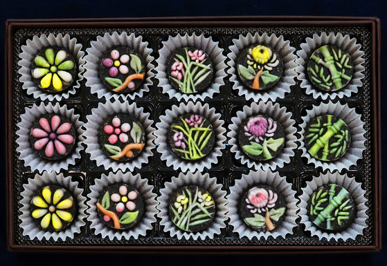 Black sesame 'dasik,' or bite-sized desserts made of powdered grain and nuts, sprinkled with steamed white rice cake powder. [PARK SANG-MOON]