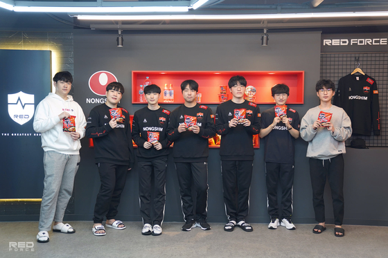 Members of Nongshim RedForce line up, each with a Shin Ramyun packet in hand, for a group photo at their training facilities. [NONGSHIM REDFORCE]