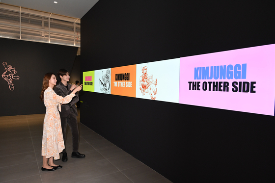 Models look at artist Kim Jung-gi's exhibition on an LG Electronics' video wall at Lotte World Tower in southern Seoul on Wednesday. [YONHAP]