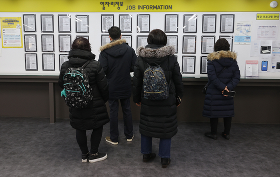 People look at a bulletin board at a job center in Mapo District, western Seoul on Jan. 13. Due to Covid-19, job losses last year were the largest since the Asian economic crisis of the 1990s. [YONHAP]