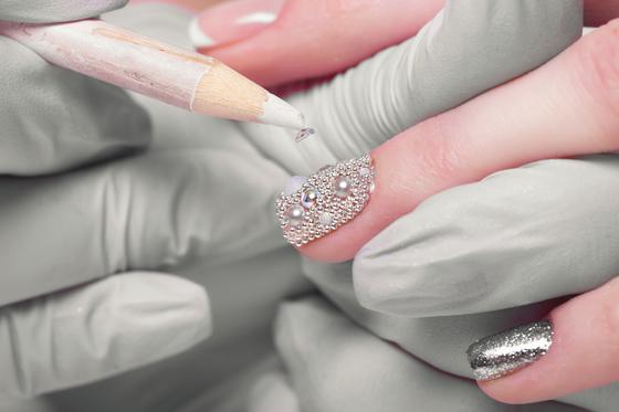 A nail artist applies rhinestones on a client's nails. [SHUTTERSTOCK]