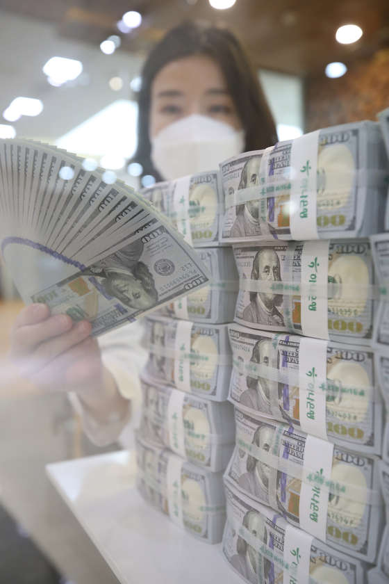 An employee organizes stacks of dollar bills at Hana Bank's Counterfeit Notes Response Center in Jung District, central Seoul on Thursday. According to the Bank of Korea (BOK), Korea's foreign exchange reserve at the end of April was $452.3 billion, up $6.2 billion on month. This is also higher than the record of $448 billion at the end of February. [YONHAP]