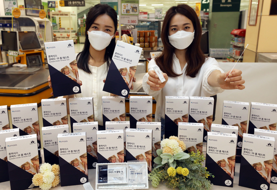 Models pose with Humasis Covid-19 test kits at Emart's Seongsu branch in eastern Seoul on Thursday. Emart is the first discount mart in Korea selling the test kits. [YONHAP]