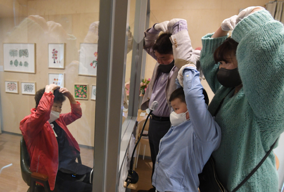 A family visits their grandmother in a convalescent hospital in Seongdong District, eastern Seoul, on Thursday, two days ahead of Parents' Day. The relatives were separated by a window to prevent transmission of Covid-19.  [YONHAP]