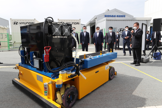 President Moon Jae-in, second from left, listens to explanations about a hydrogen-powered unmanned transport vehicle during a visit to a hydrogen fuel cell research center in Ulsan on Thursday. [JOINT PRESS CORPS]