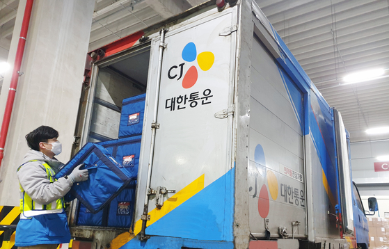 A CJ Logistics delivery worker loads packages into a delivery truck. [CJ LOGISTICS]