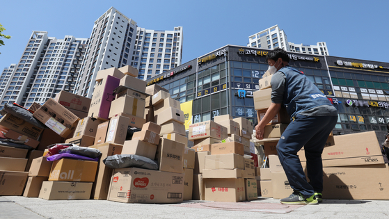 In this file photo, boxes are piled up outside an apartment complex in Godeok-dong in Gangdong District, eastern Seoul, on April 11, after its residents banned freight trucks from entering the ground floor of the compound. Delivery workers left the boxes at the main gate in protest. [NEWS1]