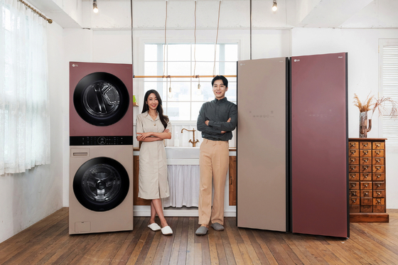 Models pose with new colors of LG Objet Collection styler and Wash Tower, a washer-dryer combo. The new colors are Clay Brown and Red Wood. [YONHAP]