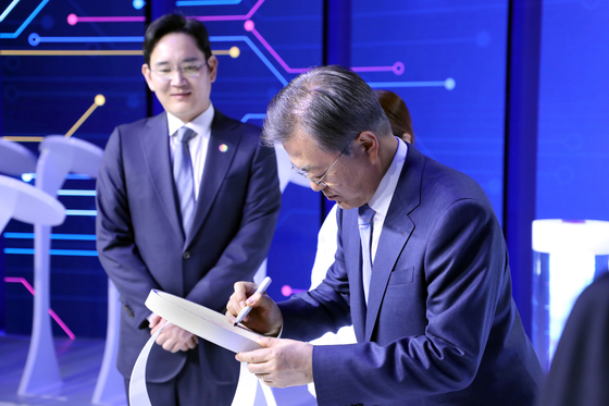 """Flanked by Samsung Electronics' Vice Chairman Lee Jae-yong, left, in its Hwaseong plant on April 2019, President Moon Jae-in signs on the world's first 7-nanometer circuit wafer the company developed using extreme ultraviolet (EUV) lithography equipment on the sidelines of the government declaration of the """"System Semiconductor Vision."""" [YONHAP]"""