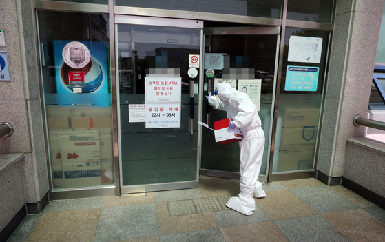A health official enters the nursing hospital in Yeosu, South Jeolla, on Sunday, where 10 patients have been newly diagnosed with Covid-19 since a caregiver was tested positive on May 8. [YONHAP]