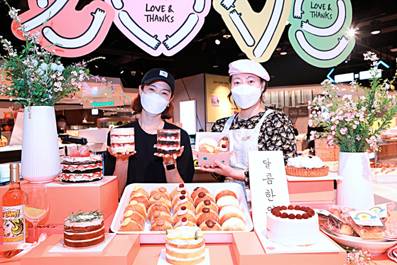 Employees pose with cakes and donuts at Lotte Department Store's Jamsil branch in southern Seoul on Monday. The department store has opened a pop-up shop selling cakes and donuts from different popular stores in Seoul until this weekend. [YONHAP]
