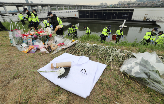 Police on Monday search for the phone of Sohn Jeong-min's friend at Banpo Han River Park, now lined with commemorative flowers. [NEWS1]