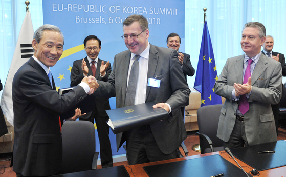 At front, Korea's Trade Minister Kim Jong-hoon, left, and Belgian Foreign Minister Steven Vanacker shake hands after signing the European Union-Korea FTA on Oct. 6, 2011, in Brussels, Belgium. Behind them, Korea's President Lee Myung-bak, left, and European Commission's President Josse Manuel Barroso celebrate the signing of the FTA. [JOINT PRESS CORPS]