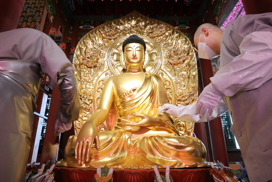 Monks clean a statue of Buddha in the main hall of Jogye Temple in Jongno District, central Seoul, on Tuesday, a week ahead of Buddha's Birthday on May 19 this year. [NEWS1]