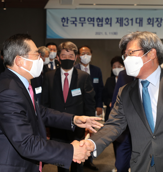 Korea International Trade Association (KITA) Chairman Koo Ja-yeol, left, shakes hands with a KITA executive during the first meeting of the association's 31st board at Trade Tower in Samseong-dong, southern Seoul, on Tuesday. The meeting introduced members of the 31st board, including 15 new representatives. [YONHAP]