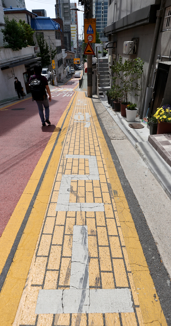 A man walks next to the Children Protection Zone near an elementary school in Seoul on Tuesday. The Seoul Metropolitan Government has raised the fine for illegally parked vehicles in such zones from 80,000 won ($72) to 120,000 won, while the fine for vans increased from 90,000 won to 130,000 won. [YONHAP]