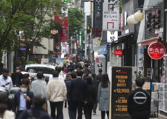 People crowd a street in Myeong-dong, Seoul, an area that was hit hard by Covid-19 outbreak. Increasing economic activity is contributing to tax revenue. [YONHAP]
