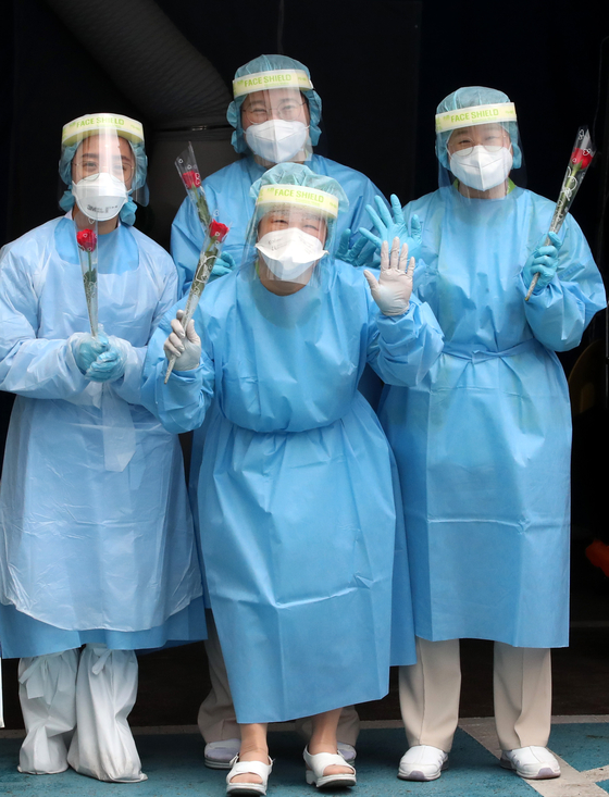 At a Covid-19 test site at St. Mary's Hospital in Daejeon, nurses wearing protective gear hold roses which the hospital management handed out on Tuesday, a day ahead of International Nurses' Day which falls on May 12. [NEWS1]
