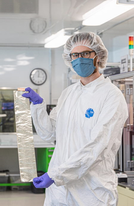A researcher at SolidEnergy Systems holds foil used for lithium metal batteries. [SK INC.]