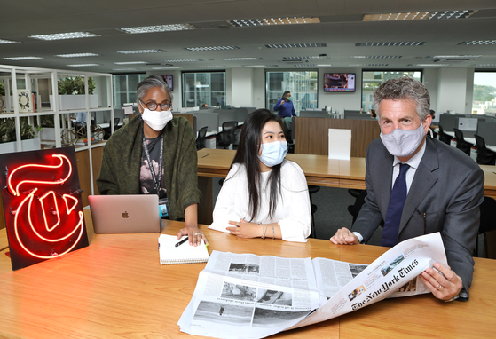 Stephen Dunbar-Johnson, international president of The New York Times Company, right, chats with the newspaper's staff at the paper's new Asia hub in Jongno District, central Seoul, Tuesday. From left, Lauretta Chalton, an editor with the Times, and Elsie Chen, a researcher. [PARK SANG-MOON]