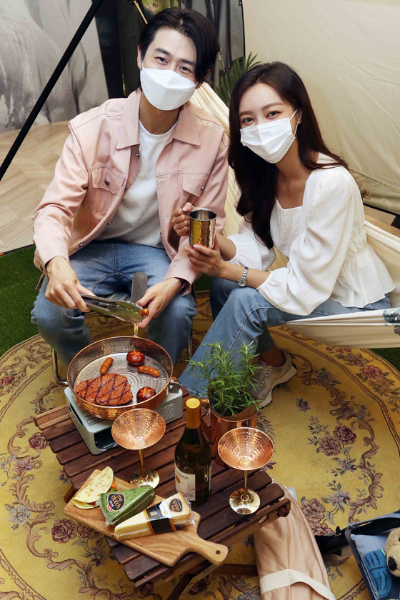 Models pose with camping equipment to promote Shinsegae Department Store's Terrace Home Camping event at the department store's main branch in Myeong-dong, central Seoul, on Thursday. The event runs from Thursday until May 31, offering a variety of camping equipment from brands such as Basil Bangs, Lumiere 9 and Hatton Heritage. [YONHAP]