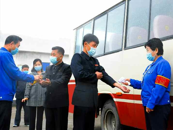 North Koreans in masks get temperature checks before boarding a bus in Pakchon County in North Pyongan, pictured in an article run by the state-run Rodong Sinmun on Covid-19 quarantine measures Tuesday. Pyongyang claims that it has no Covid-19 cases. [RODONG SINMUN]