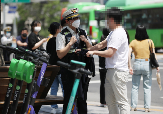 A police officer stops an electric scooter driver in Hongdae, western Seoul, on Thursday. According to an amendment to the Road Traffic Act, unlicensed e-scooter riders are subject to a 100,000 won fine from Thursday. Those caught riding without helmets face a 20,000 won fine. A 40,000-won fine is imposed if two or more people are seen riding an e-scooter. [YONHAP]