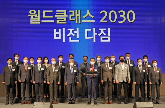 Oh Suk-song, chairman of Korea World Class Enterprise Organization, center, and representatives from 19 companies that have been selected for the second World Class project, pose for a photo during a vision declaration ceremony held at the Seoul Dragon City hotel in Yongsan District, central Seoul, on Friday. [PARK SANG-MOON]