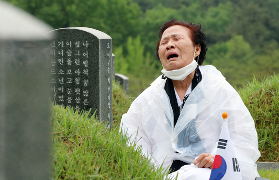 A woman sobs at her child's tombstone in the May 18th National Cemetery in Gwangju on Monday. Her child is one of hundreds of victims who were killed by soldiers who clamped down on the democratization movement in Gwangju in May 1980. [YONHAP]