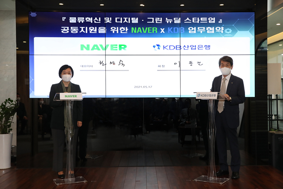 Korea Development Bank Chairman Lee Dong-gull, right, and Naver CEO Han Seong-sook pose for a photo after signing a partnership Monday to help the Dongdaemun fashion district in Seoul. [KOREA DEVELOPMENT BANK]
