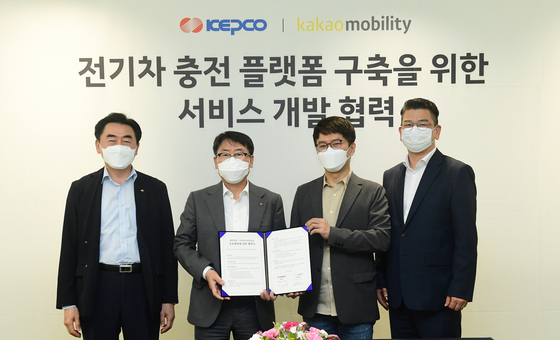 Lee Jong-hwan, Kepco Vice President. second from left, and Alex Ryu, Kakao Mobility CEO, second from right, hold up a signed MOU at Kakao Mobiilty's headquarters in Seongnam, Gyeonggi, on Friday. [KEPCO]