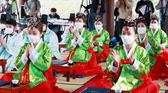Young people dressed in hanbok, or traditional Korean attire, who have reached the age of adulthood, clap during a ceremony to mark the 49th anniversary of the Coming-of-age Day at the Hanok Village in Jung District, central Seoul, on Monday. [NEWS1]