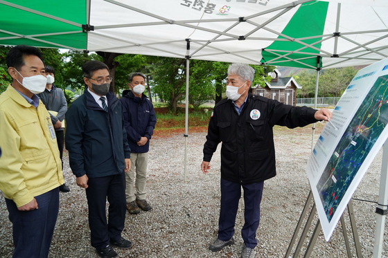Choi Byeong-am, second from left, chief of the Korea Forest Service, inspects logging sites at Duchon-myeon in Hongcheon County in Gangwon Monday afternoon alongside local officials. The Forest Service aims to plant 3 billion young trees over the next 30 years after logging aged trees in an attempt to offset carbon emissions, a plan being criticized by environmental activists. [NEWS1]